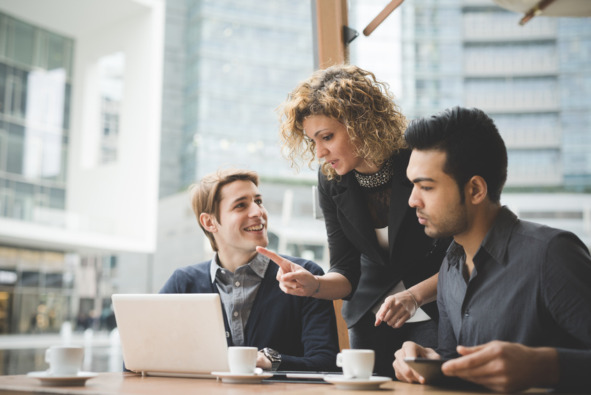 Multiracial contemporary business people working connected with technological devices like tablet and laptop, talking together - finance, business, technology concept
